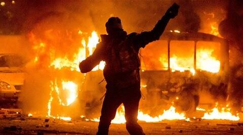 A protester throws a stone towards a burning police bus in front of him, during clashes with the police, in central Kiev on Sunday night. (AP)