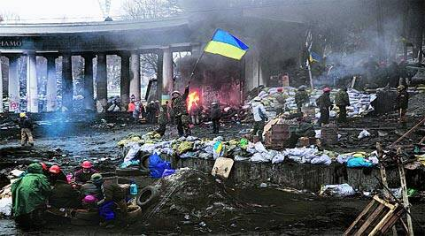 An anti-government protester waves the Ukrainian flag at the site of clashes in Kiev Tuesday. reuters