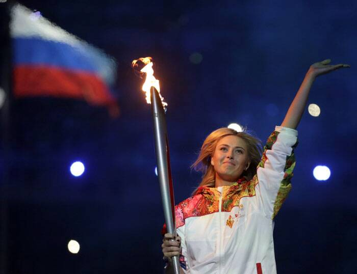 Russia's Tennis player, Maria Sharapova carries the torch during the opening ceremony of the 2014 Winter Olympics in Sochi, Russia on Friday. (AP)