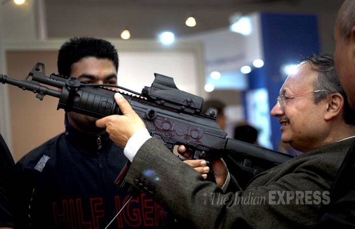 A delegate tries his hands on an assault rifle during the Defexpo India 2014 in New Delhi on Thursday. (IE Photo: Oinam Anand)