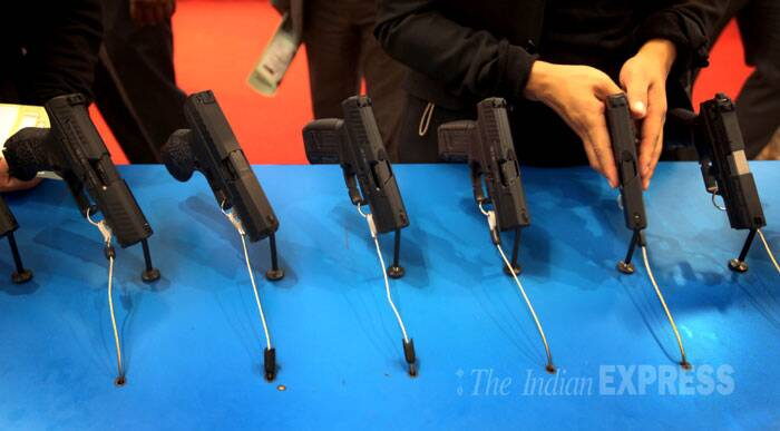 A visitor tries a hand gun at Defexpo India 2014 in New Delhi on Thursday. (IE Photo: Oinam Anand)
