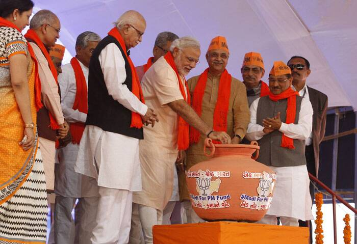 "Gujarat Chief Minister and BJP's prime ministerial candidate Narendra Modi and senior BJP leader LK Advani drop a Rs 1000 note in a pitcher marked ""Modi-for-PM fund"". (Reuters)"