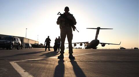 This Dec. 8, 2013 file-pool photo shows a solider standing guard near a military aircraft in Kandahar, Afghanistan.