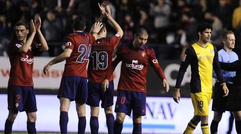 Atletico de Madrid's Diego Costa of Brazil, right, leaves the pitch while Osasuna's Roberto Torres, Damia Abella, Oriel Riera, and Emiliano Armenteros of Argentina, left to right, celebrate after they won the match 3-0 (AP)