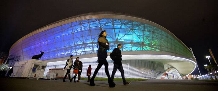 Spectators walk past Adler Arena, home of the long track speed skating competitions, on their way to the rehearsal of the opening ceremony at the 2014 Winter Olympics. (AP)