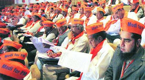BJP members wearing saffron-coloured AAP-style caps attend the party's executive meeting in Gandhinagar on Friday. (IE)