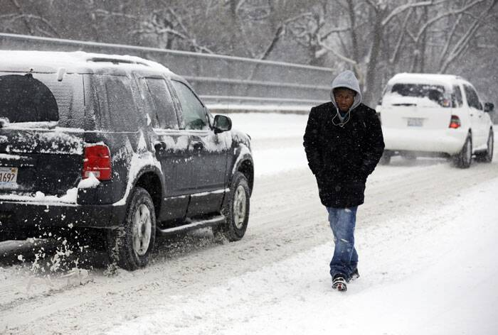 Jimmy Barnes walks on the sidewalk during a heavy snow day in Skokie. (AP)