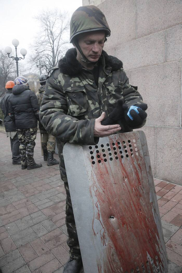 An activist holds a shield with a bullet hole, covered with the blood of his comrade killed in clashes with police, in Kiev's Independence Square, the epicenter of the country's current unrest. Fierce clashes between police and protesters in Ukraine's capital have shattered the brief truce Thursday and a reporter has seen dozens bodies laid out on the edge of the protest encampment. (AP)