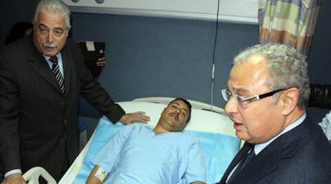 Governor of South Sinai, Major General Khaled Foda, left, and Egyptian Minister of Tourism Hesham Zazou, second right, visit an unidentified Egyptian who was wounded in the bus explosion.