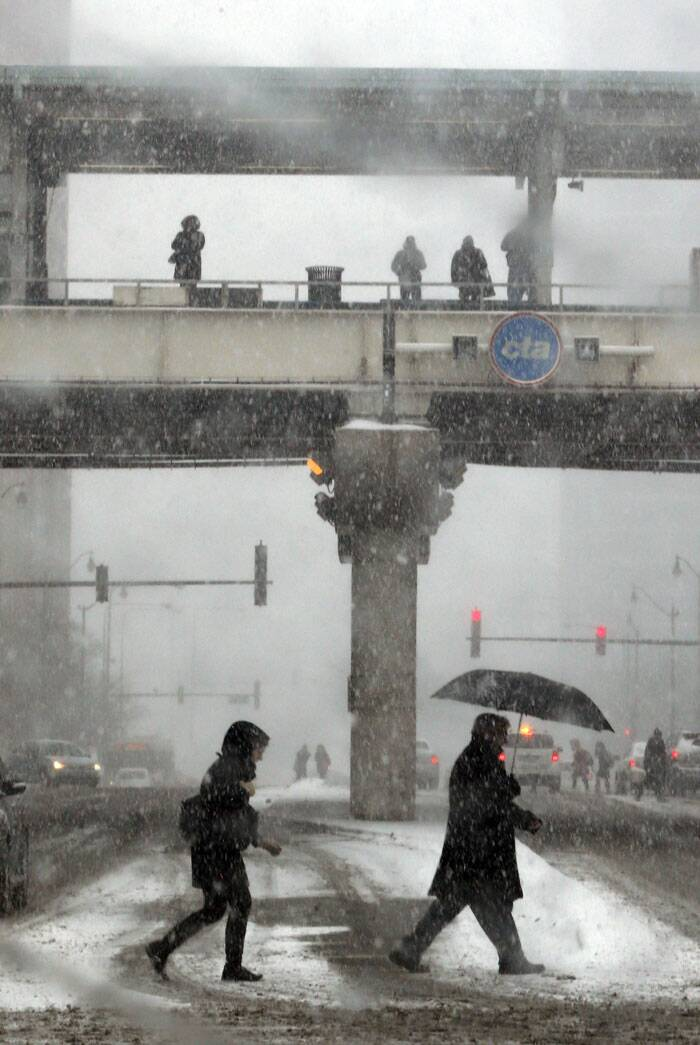 Pedestrians walk across an intersection as others wait on an elevated train station during a snowstorm. (AP)