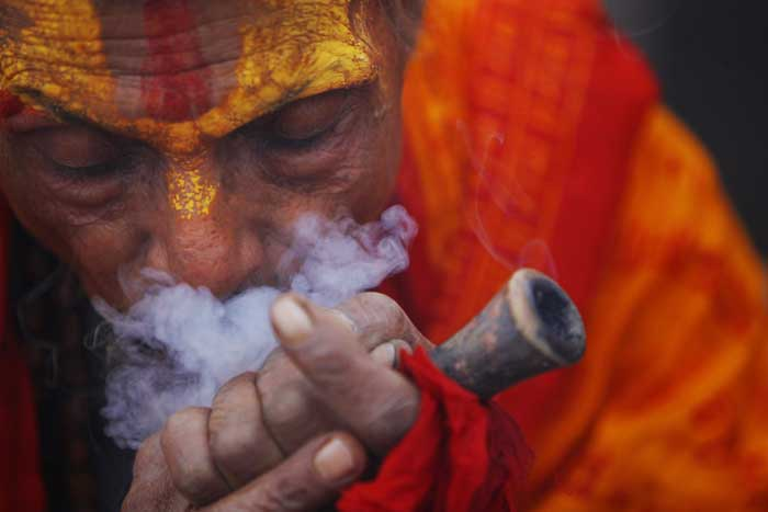 A Hindu holy man smokes marijuana in the courtyard of the Pashupatinath Temple in Katmandu, Nepal. (AP)