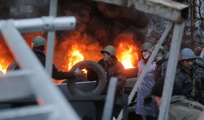 Activists burn tyres at barricades close to Independence Square, the epicenter of the country's current unrest, in Kiev, Ukraine. <br /> Heavy black smoke rising from burning tyres does not allow riot police snipers hold aimed fire against protesters. (AP)