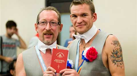 Russian newlyweds Alexander Emereev, left, and Dmitry Zaytsev pose with their marriage book in Buenos Aires, Argentina. (AP