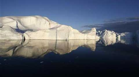 Icebergs reflected in the calm waters at the mouth of the Jakobshavn ice fjord near Ilulissat in Greenland. (Reuters)
