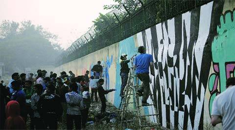The graffiti wall of the government school in Dwarka; Brazilian artist Sergio with his work.