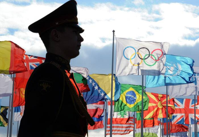 A guard stands at attention in front of the Olympic flag and flags of the United Nations and countries participating in the 2014 Winter Olympics. (AP)