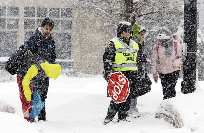 Students wait to cross the street during a heavy snow day in Glenview. (AP)