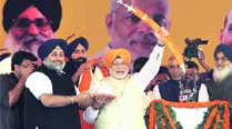 BJP's PM candidate Narendra Modi being honoured by Punjab Dy CM Sukhbir Badal, while Rajnath Singh and Parkash Singh Badal look on during the Fateh Rally in Ludhiana on Sunday. 	Gurmeet Singh
