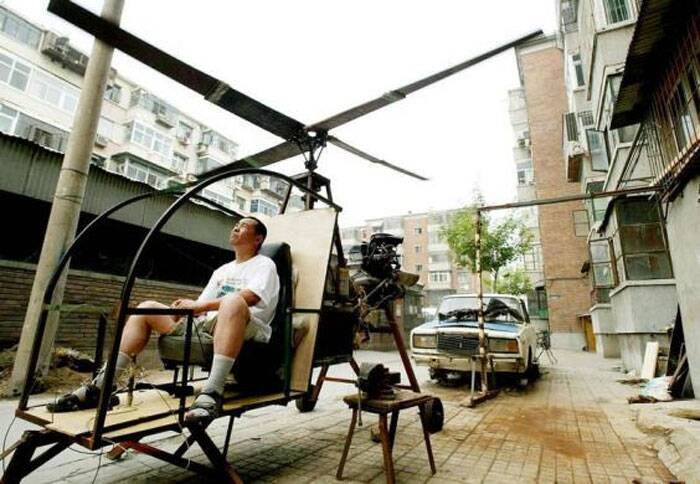 "A self-styled Chinese inventor tests his homemade helicoptor next to his apartment in Beijing June 25, 2003. Yu Jun follows in the footsteps of his younger brother who lost his life in a national park in central China at the end of a 20 year search for the legendary ""Bigfoot"", and intends to continue the quest from the sky. Without any formal education in aerospace science, Yu Jun spent five years constructing the helicopter from spare parts belonging to a dilapidated ""Lada"" automobile (in back). (Reuters)"