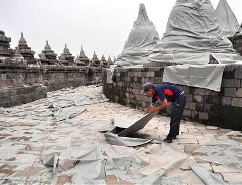 A worker spreads plastic sheets to cover Borobudur temple to protect from volcanic ash, from an eruption of Mount Kelud, in Magelang, central Java, Indonesia, Friday, Feb. 14, 2014.
