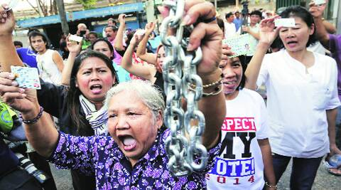 Protesters demanding the right to vote break into the district office, chained earlier by  anti-government protesters, after voting was called off in a Bangkok district Sunday. reuters