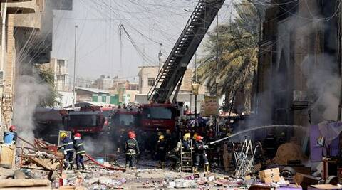Iraqi firefighters try to extinguish fire after two bombs went off in Baghdad. (AP)