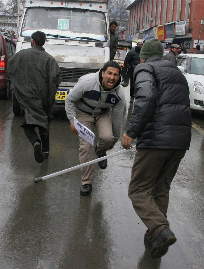 A policeman beats one of the Government Public Health and Engineering (PHE) employees during their protest march in support of their long pending demands at Lal Chowk in Srinagar on Saturday. (PTI)