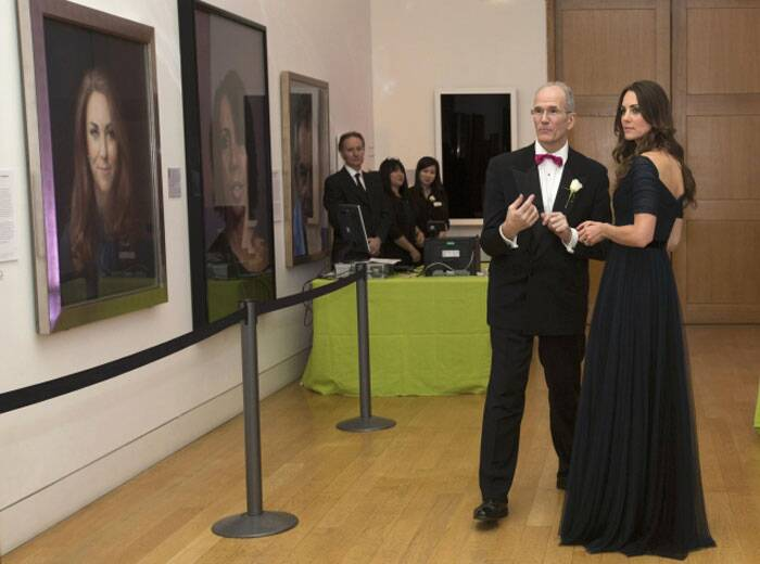 Kate Middleton is escorted by National Portrait Gallery's Director Sandy Nairne as they stand opposite a portrait of the Duchess during the Portrait Gala 2014. (Reuters)