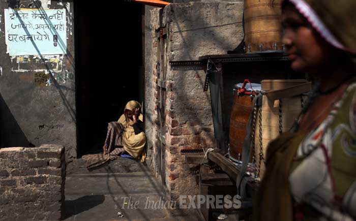 An old woman sits on her doorstep with a poster on the wall warning the residents of Kathputli Colony to save the colony. (IE Photo: Oinam Anand)