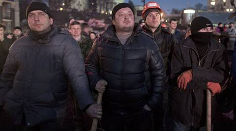 Anti-government protesters watch a live broadcast from the parliament in central Kiev, Ukraine, Friday, Feb. 21, 2014.