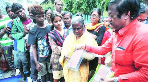 Jyotipriyo Mullick distributes rations cards to the homeless, in Kolkata on Thursday. Subham Dutta