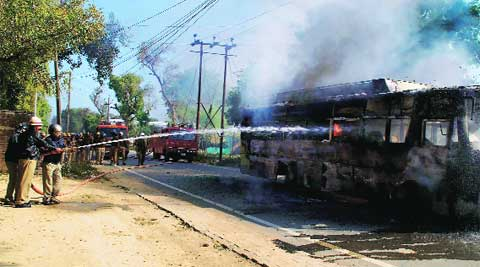 Firemen douse a bus set ablaze during a protest after a clash at Jhunsi, in Allahabad on Monday.PTI