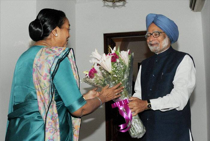 Lok Sabha Speaker Meira Kumar greets Prime Minister Manmohan Singh at his residence in New Delhi on Saturday. (PTI)