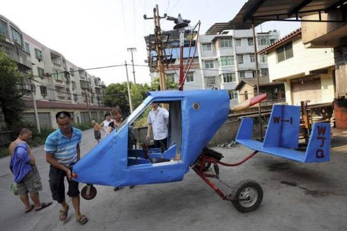 Wen Jiaquan (2nd L), 54-year-old motorcycle mechanic, moves his self-made helicopter in Qingping township of Chongqing municipality, July 28, 2013. Wen and his family spent over 10,000 yuan (1,630 USD) and more than three months to build this 4.2-metre-long, 2.8-metre-high helicopter using mostly motorcycle components and a used car engine, local media reported. Picture taken July 28, 2013. (Reuters)