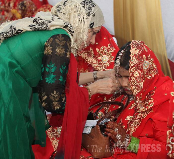 A relative adjusts a bride's jewellery before the wedding. (IE Photo: Dilip Kagda)