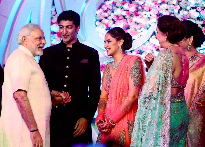 Narendra Modi holds the groom's hand as he chats with mother of the bride BJP MP Hema Malini and Ahana Deol. <br /><br /> Post her wedding with Vaibhav, Ahana will be shifting base to New Delhi. (PTI)