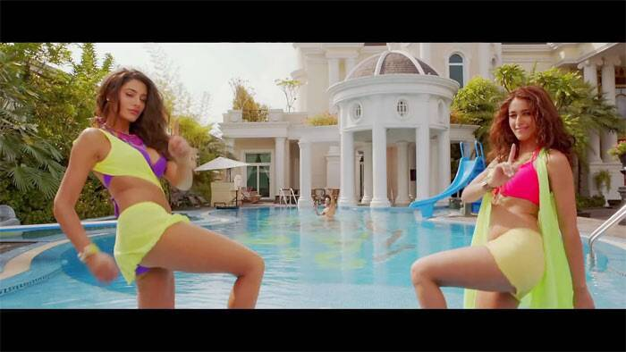 Bikini babes Nargis Fakhri and Ileana D'cruz turn up the heat in a sizzling hot still from their upcoming flick, 'Main Tera Hero' also starring Varun Dhawan. The actresses flaunt their perfectly toned figure in colourful bikinis.