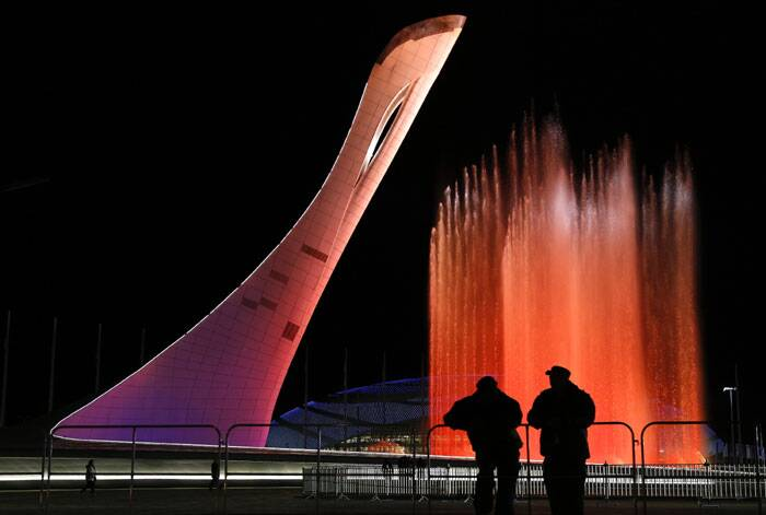 Security personnel watch a practice run of a fountain show to music from 'Swan Lake' on the perimeter of the Olympic cauldron in preparation for the 2014 Winter Olympics. (AP)