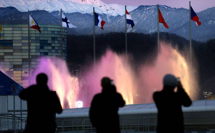 Spectators photograph water fountains at Olympic Park during final preparations before the 2014 Winter Olympics in Sochi, Russia. (AP)