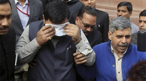 An unidentified member of India's parliament covers his face with a handkerchief after being affected by pepper spray gas in New Delhi. (Photo:AP)