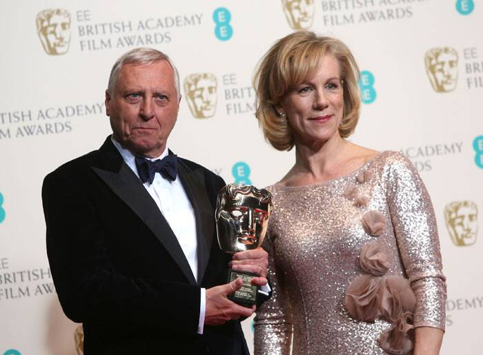 Winner of outstanding contribution Peter Greenaway shows off his BAFTA as he poses with Juliet Stephenson. (AP)