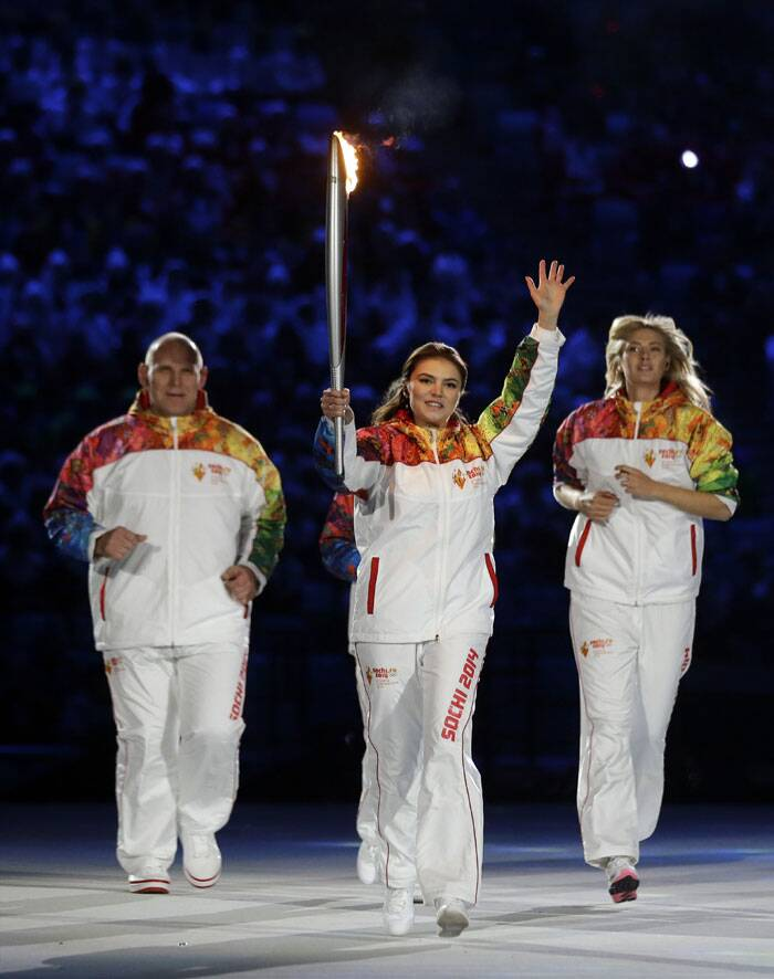 Alina Kabaeva holds the torch flanked by Maria Sharapova, right, and Alexandr Karelin during the opening ceremony of the 2014 Winter Olympics in Sochi. (AP)