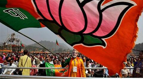 An Indian supporter wears a mask of India's main opposition Bharatiya Janata Party's (BJP) Prime Ministerial candidate Narendra Modi as he waves the party flag at a public rally. (AP Photo)