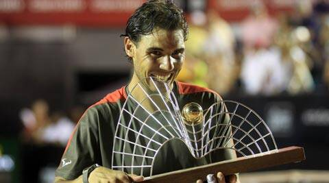 Rafael Nadal of Spain bites his trophy after winning against Alexandr Dolgopolov of Ukraine at the 2014 Rio Open men's final tennis match (Reuters)