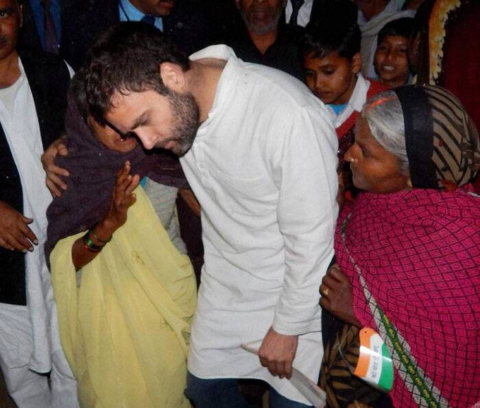 The local MP was on a tour of his parliamentary constituency today. He held 'chaupal' (meetings) in villages and criticised the Samajwadi Party government for poor state of roads and power in Amethi. <br /> Congress Vice President Rahul Gandhi interacts with an old lady during foundation stone laying ceremony of Rail Neer bottling plant at Gauriganj in Amethi, Uttar Pradesh. (PTI)