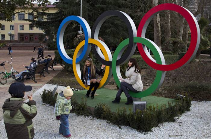 Russian women pose for snapshots next to Olympic rings in Sochi, Russia. The opening ceremony for the 2014 Winter Olympics will be held on February 7, and the competition will run until February 23. (AP)