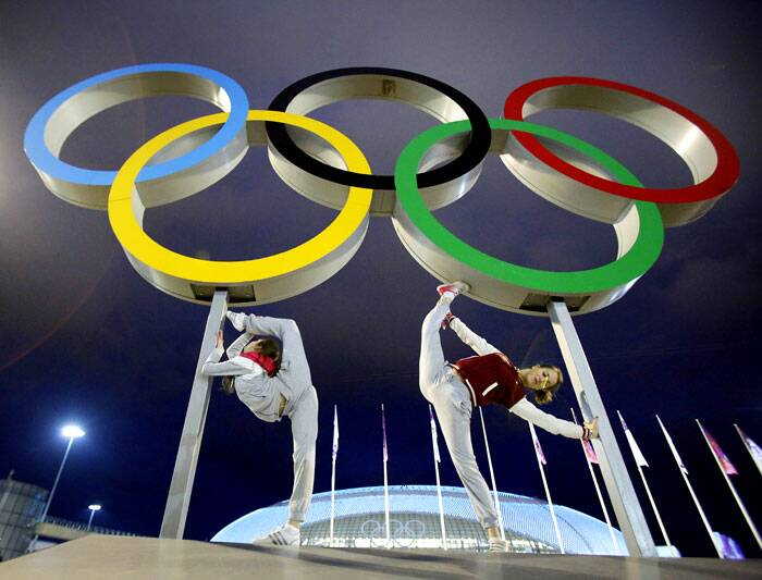 Russian dancers who will be performing at the opening ceremony pose with the Olympic rings as their friend photographs them, ahead of the 2014 Winter Olympics. (AP)