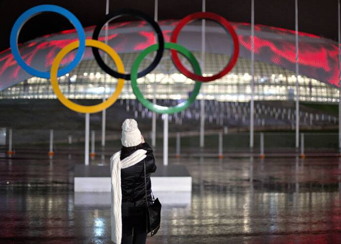 Andreevna Mariya Smorodskaya, a make-up artist for the opening ceremonies, takes a photo of the Olympic rings against the Bolshoy Ice Dome during a roof light display of moving flames, at the 2014 Winter Olympics. (AP)