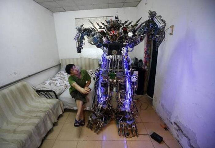 "Chinese inventor Tao Xiangli controls his self-made humanoid robot with a remote controller as he poses with it during a photo opportunity at his house located in a old residential area in Beijing August 8, 2013. The self-taught Chinese inventor built the home-made robot, named ""The King of Innovation"", out of scrap metal and electronic wires that he bought from a second-hand market. Tao completed his creation in less than a year, with costs of production and living expenses amounting to 300,000 yuan ($49,037). However, the robot, which measures 2.1 metres (6.9 feet) in height and 480 kg (1058 lbs) in weight, turned out to be too tall and heavy to walk out of the front door of his house. It can perform simple movements with its hands and legs and also mimic human voices.  (Reuters)"
