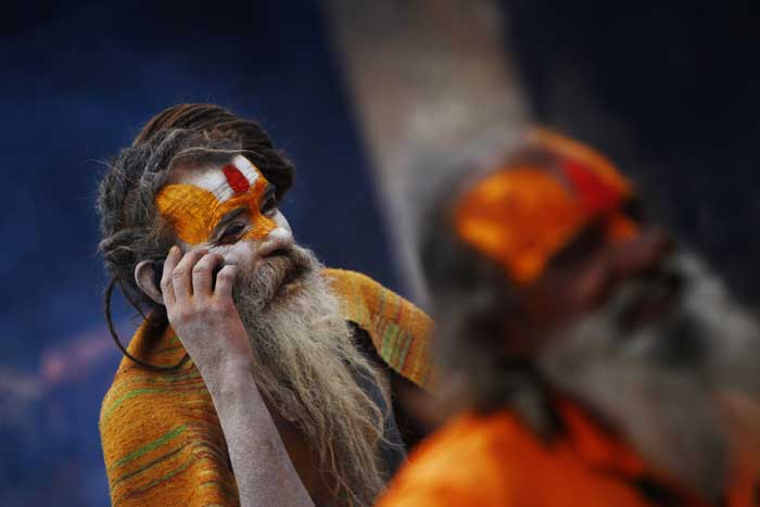 A sadhu speaks on his cell phone in the courtyard of the Pashupatinath Temple in Katmandu, Nepal. (AP)